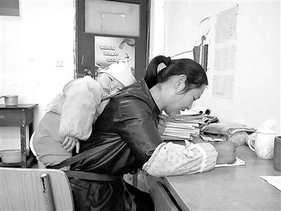 背着孩子改作业的女教师